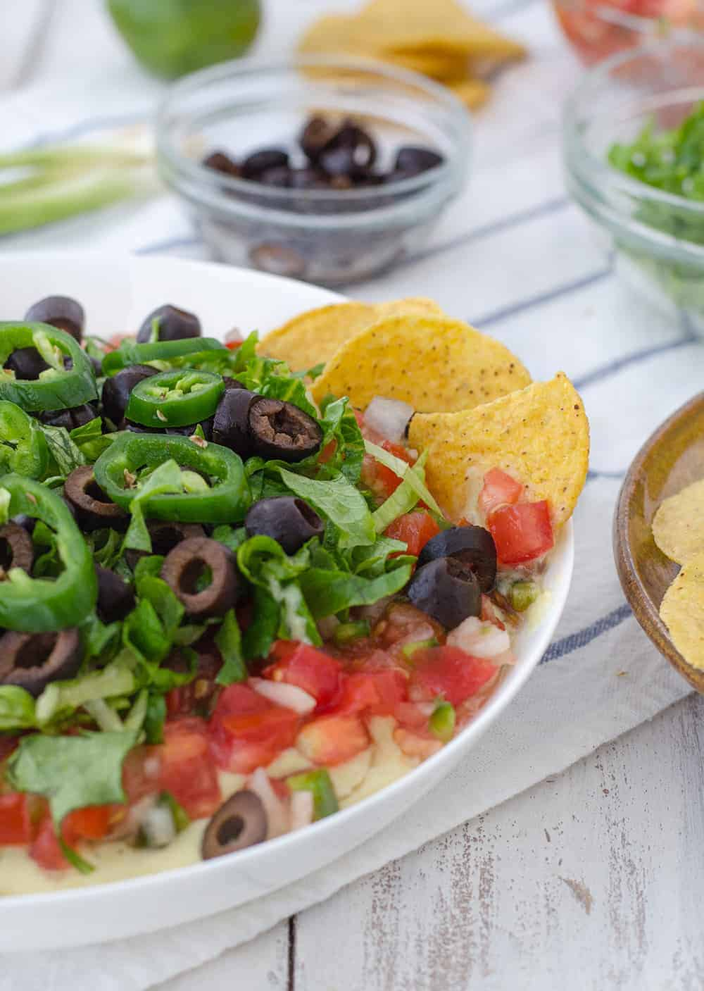 Vegan Mexican 7 Layer Dip! Refried black beans,quick vegan cheese sauce, guacamole, homemade pico de gallo, shredded lettuce, olives, and peppers! A must make for a healthy superbowl! | www.delishknowledge.com
