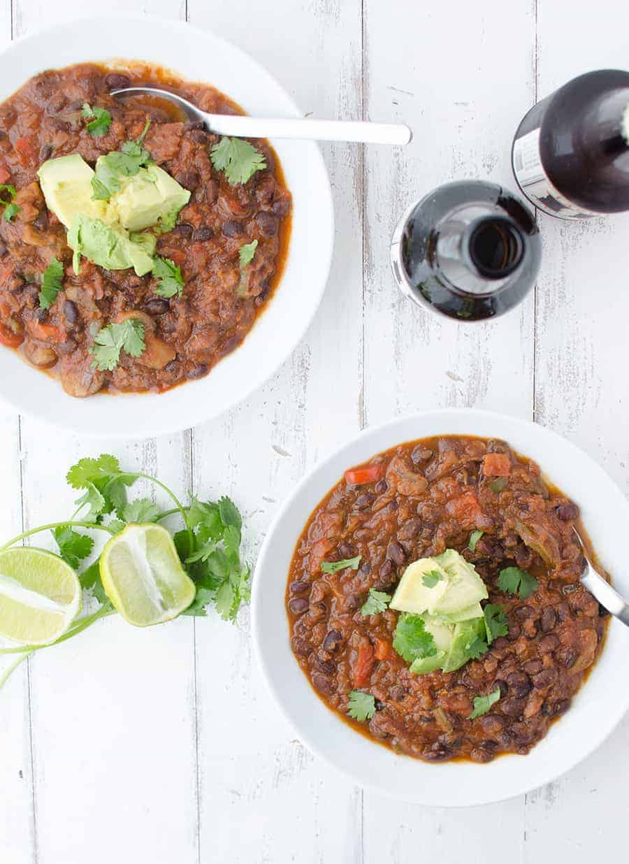 Black Bean & Beer Chili! A hearty vegetarian chili loaded with mushrooms, beans, peppers and simmered in a tangy beer sauce. 17g fiber and 22g protein in every bowl| www.delishknowledge.com