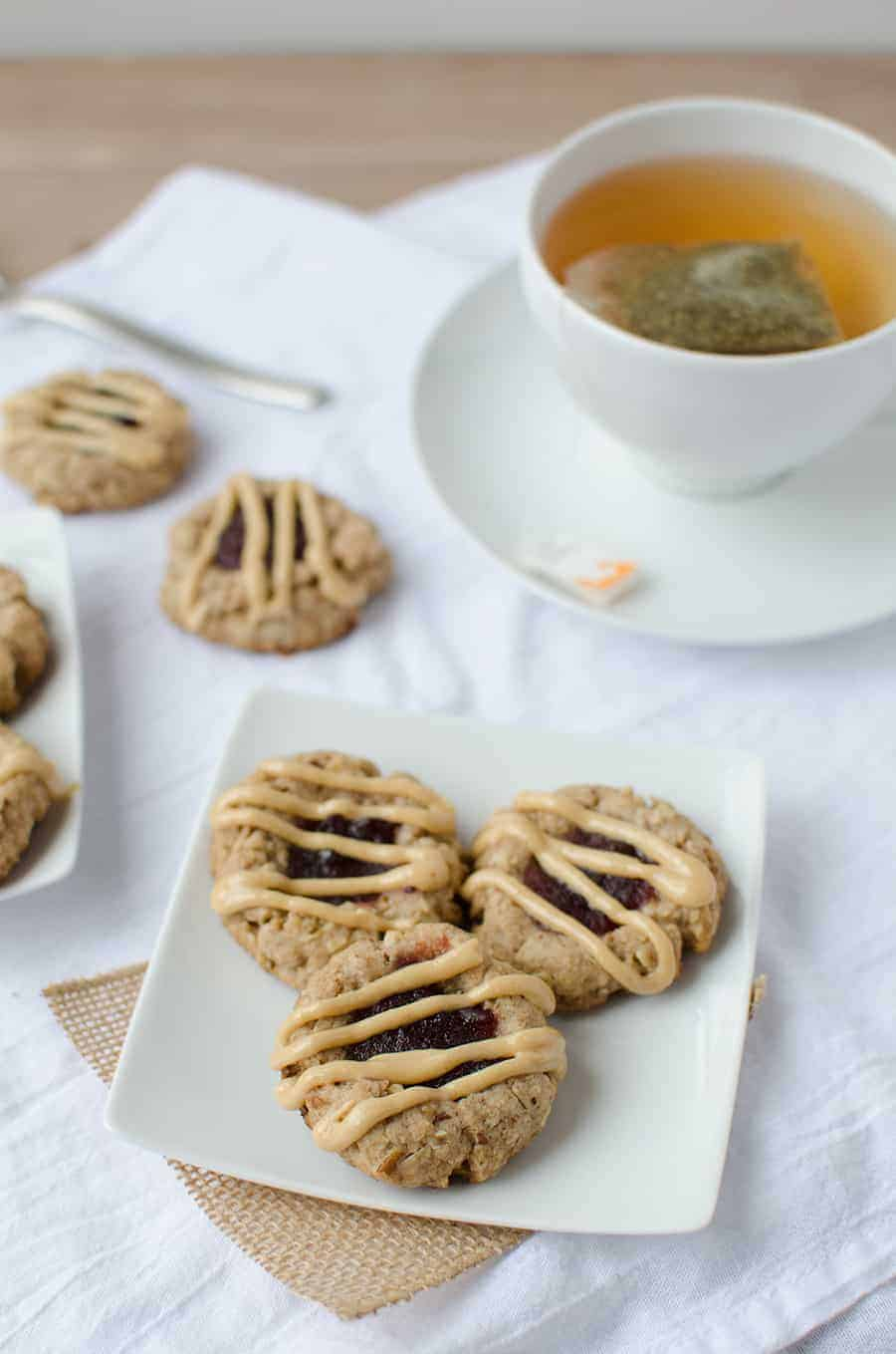 Thumbprint Cookies! Pecan cookies topped with cranberry jam and peanut butter drizzle. Wholesome, naturally sweetened and vegan! | www.delishknowledge.com