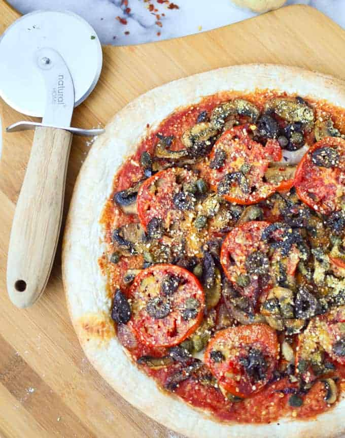 Vegan Puttanesca Pizza! You won't miss the dairy on this one. Salty olives, capers and fresh tomato slices with carmalized onions and mushrooms. Topped with homemade vegan parmasan cheese.