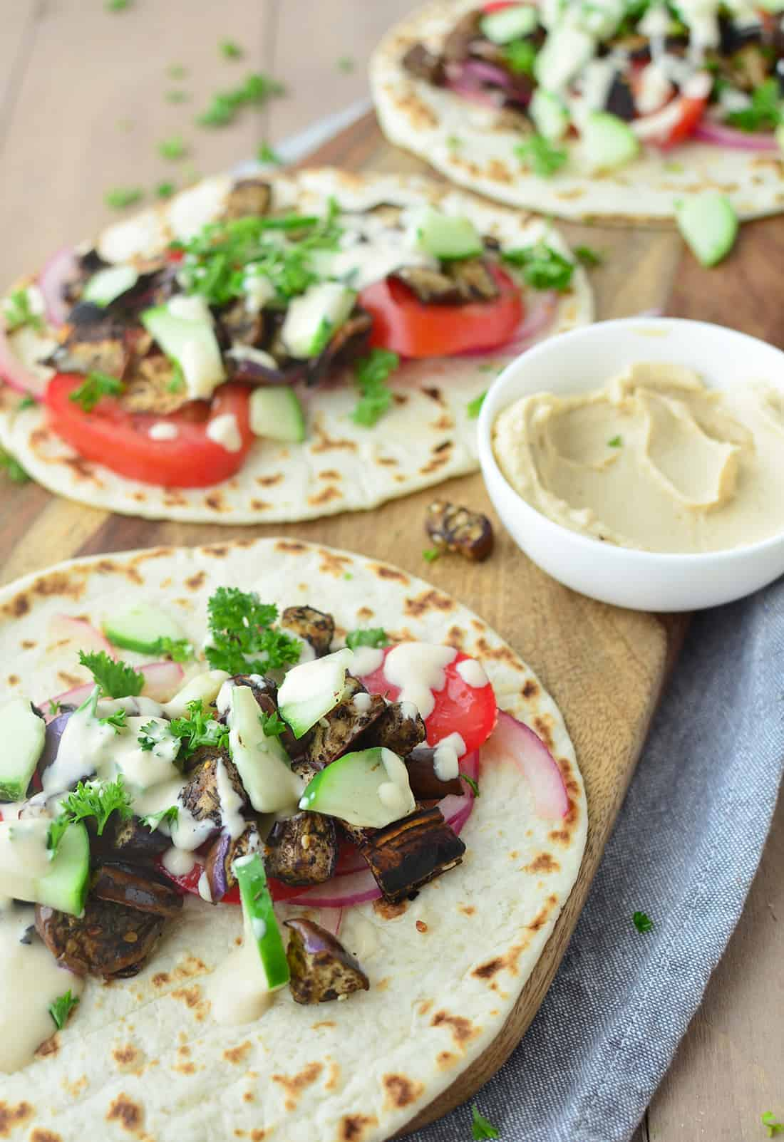 Vegan Eggplant Gyros! Zaatar seasoned eggplant stuffed into warm pita and topped with juicy tomatoes, crisp cucumbers and the BEST hummus-dill sauce. You've gotta try these! #vegan #vegetarian #healthy #sandwich | www.delishknowledge.com